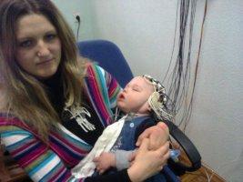 Ребенок засыпает со шлемом-шапочкой и электронной системой на голове